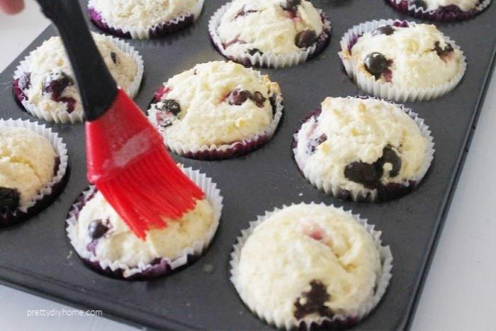 Basting fresh baked blueberry lemon muffins with lemon butter.