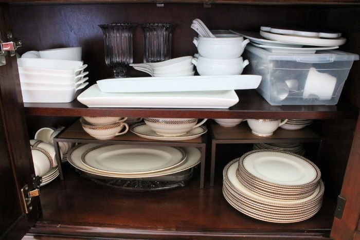 A china cabinet stacked full of dishes that will be behind closed doors. They are stacked instead of displayed but holding many dishes.