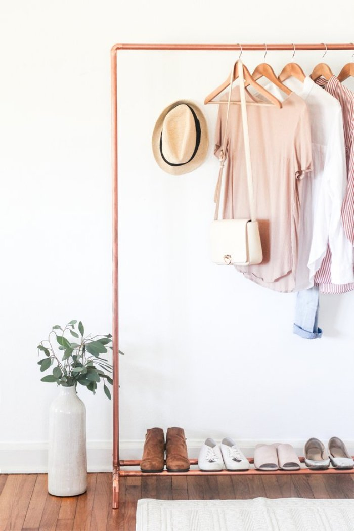 A very pretty and feminine copper pipe DIY clothing stand with a pretty casual pink wardrobe hanging from it.