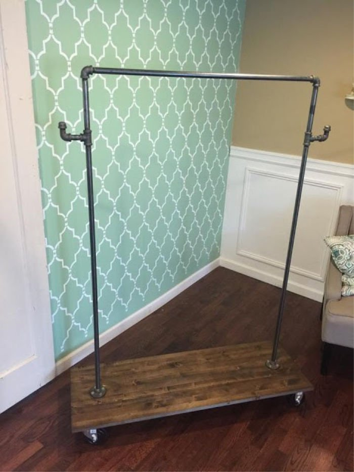 Full sized DIY clothing rack, made with pipe and has a wood base for a shoe shelf, and casters rollers.