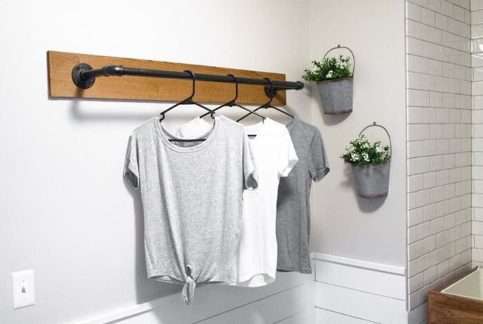 A DIY clothing rack for the laundry room. Mounted the wall and made out of wood and piping.