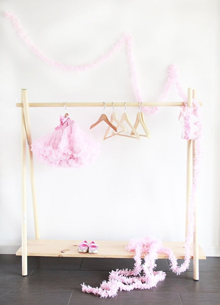 10 minute DIY clothing rack made with wood, and hanging pretty pink children's costumes