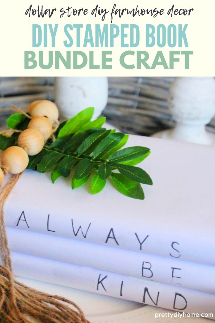 A farmhouse arrangement with diy farmhouse stamped books, tied with twine and greenery, candles and farmhouse bead.s