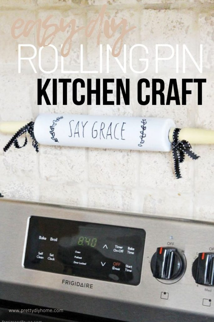 A white painted rolling pin with black lettering that says Say Grace with yellow handles, hanging over a kitchen stove as kitchen wall art.
