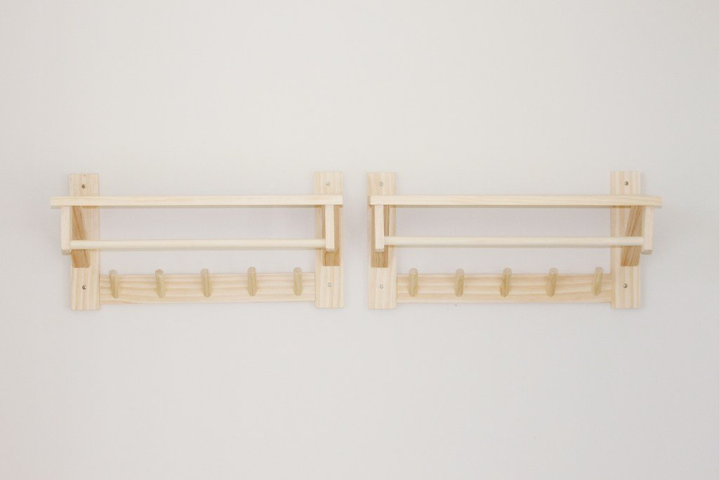 Two small wooden wall mounted DIY clothes racks for children. They are made out of natural wood and are hanging low in a closet for children.