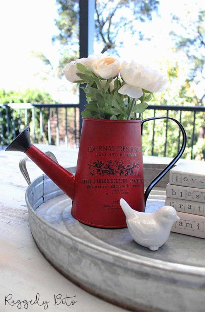 A refinished and upcycled watering can in red with black painted label.