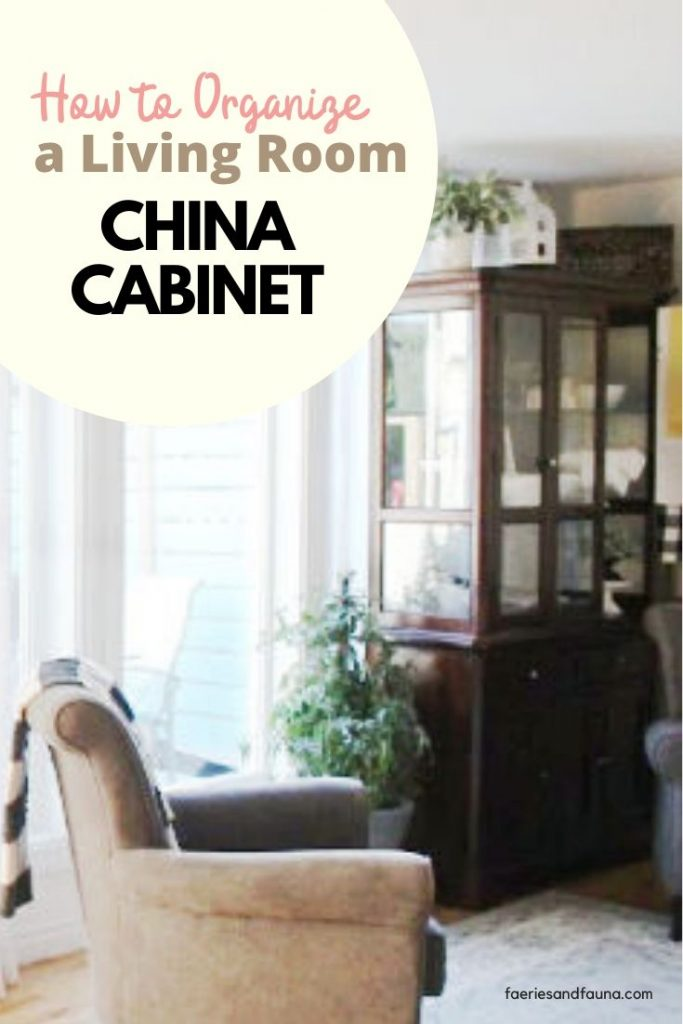 A tall glass door china cabinet in the living room decorated with white dishware and living room decor.