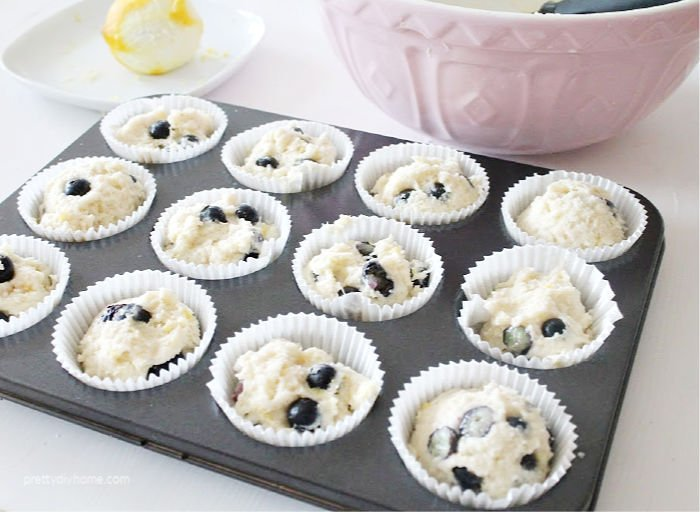 A muffin tray with 12 blueberry lemon muffins before baking.