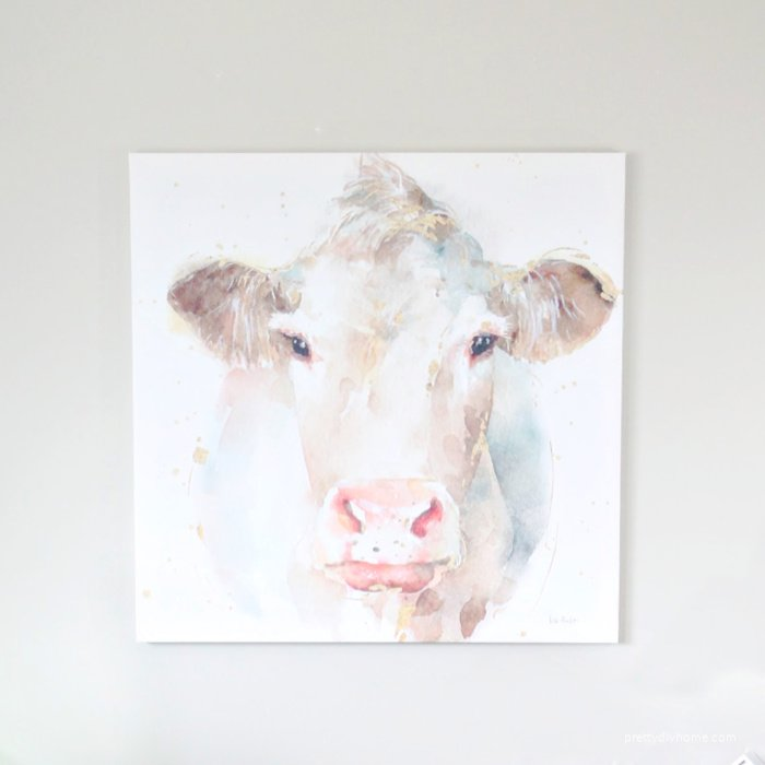 Modern Farmhouse Watercolor Cow canvas print from Photowall. Its large with pinks, grey, gold and cream.