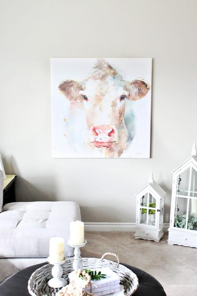 A living room wall decorated with a watercolor farmhouse cow canvas print in pretty pastel colours.