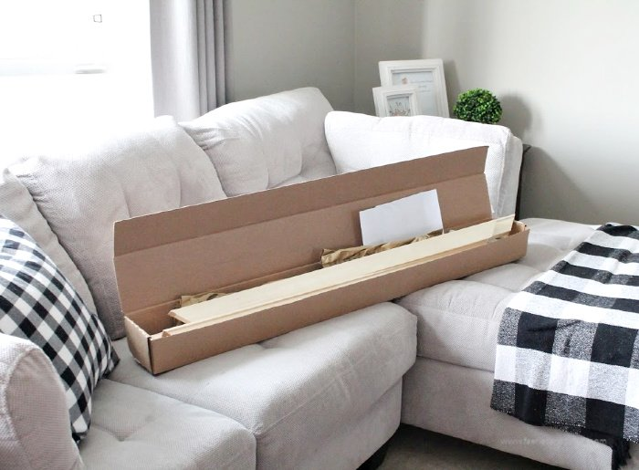A large shipping box filled with large wooden frame, instructions, and all the supplies for a canvas print.