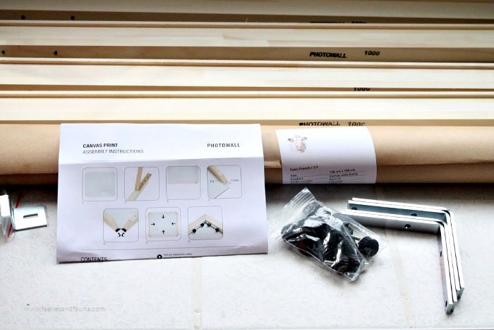 A box of supplies from Photowall for putting together a wall art canvas print. It includes printed instructions, frame, high quality canvas, and hardware.