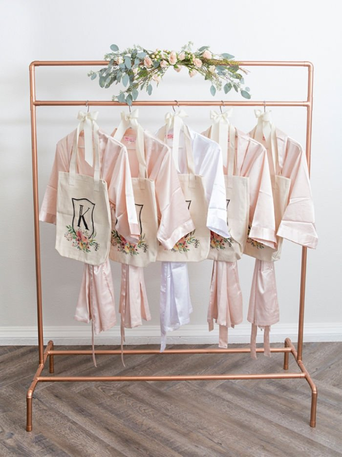 Pretty Copper Pipe Wardrobe stand with a wedding floral arrangement and four soft pink dressing gowns.