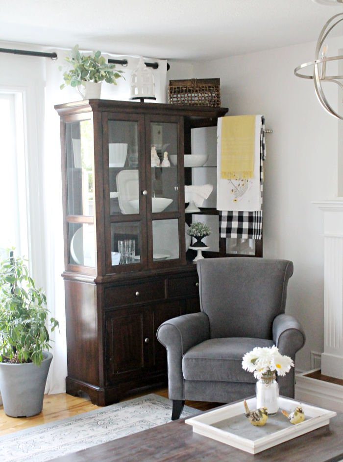 A china cabinet in the living that works because of the way its organized and decorated with all white dishes. And decorations on top that would typically be found in a living room.