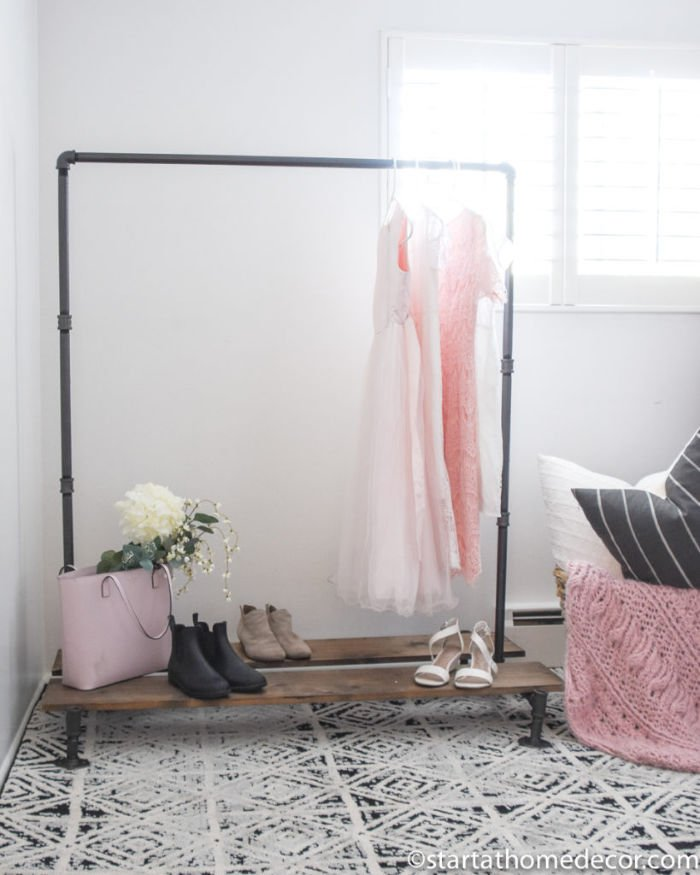 DIY clothing rack made with galvanized piping and wood shelves. It has pretty pink dresses and accessories hanging from it.