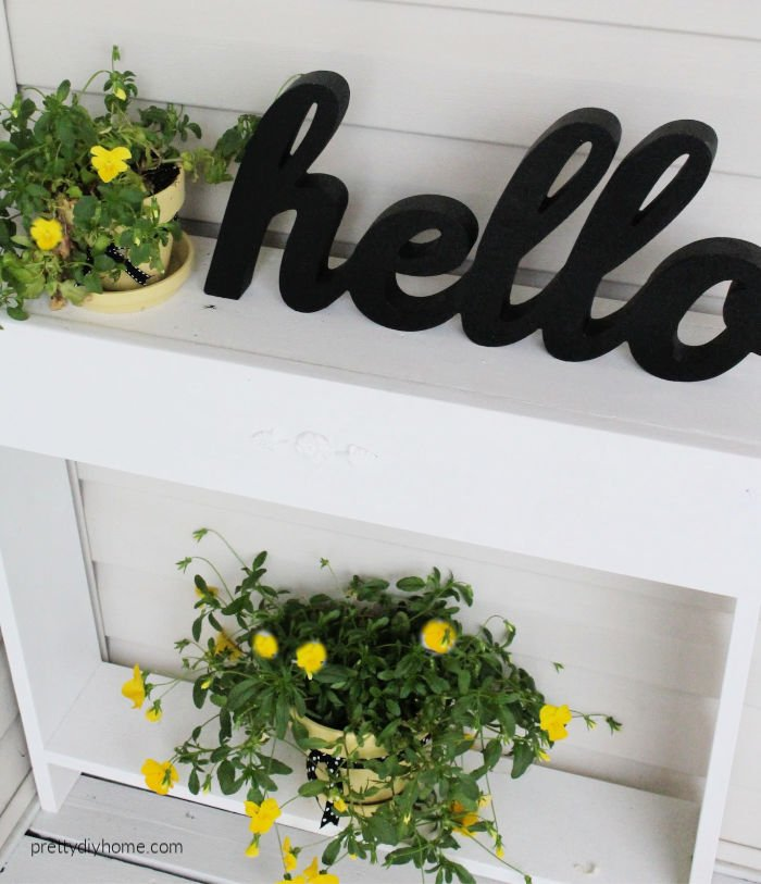 A DIY side table on a front porch with a hello sign in black, and two yellow flower pots filled with pansies.