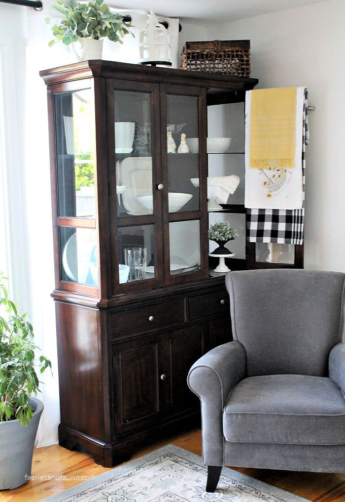 an organized china cabinet in the living room.