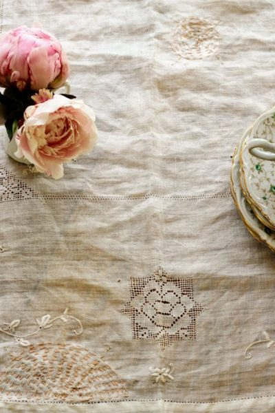 An antique tablecloth mended with pretty visible mending stitches.