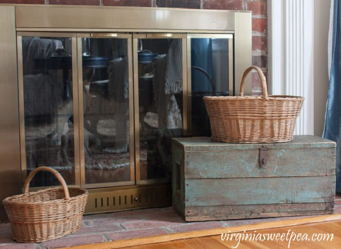 Vintage baskets and vintage creates decorating a fireplace mantel.