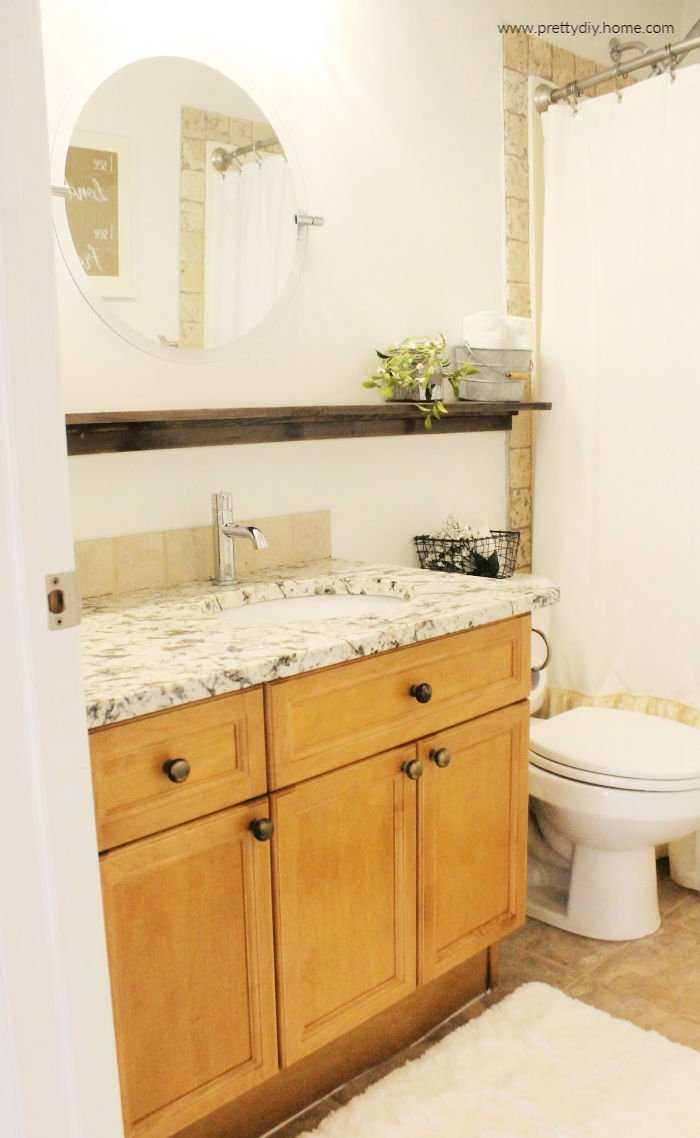 A bathroom makeover with new granite, new round mirror and wooden diy shelf.