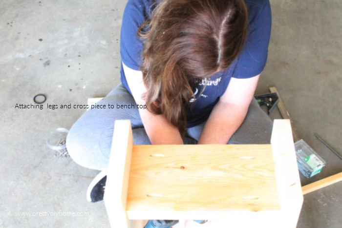 Attaching the lower portion of a wood bench to the top seat portion using a screw driver.