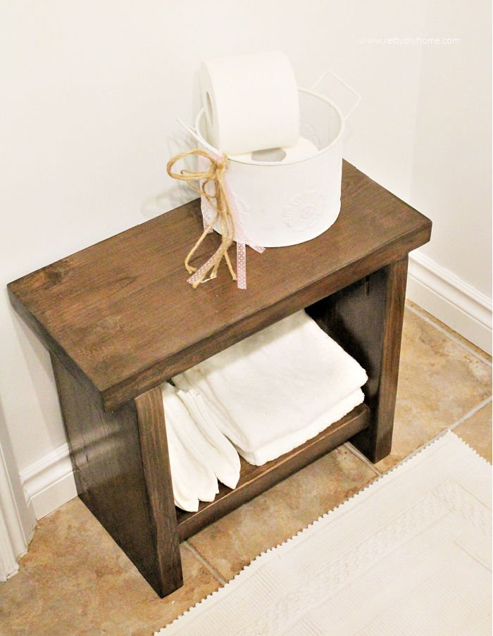 A modern farmhouse DIY milky brown bench with white towels and white farmhouse container holding white toilet paper.