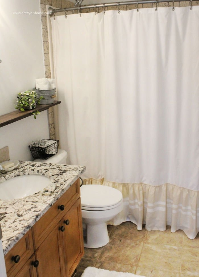 A white and cream DIY farmhouse shower curtain with white grain sack stripes on the bottom.