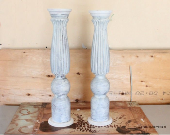 Two built wood DIY candle holders primed with Binz primer in white.