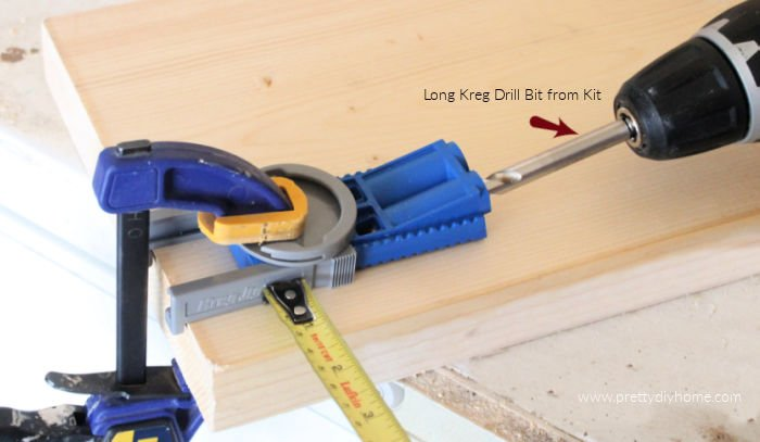 A kreg jig with a jigsaw using it to drill a hole in wood for a DIY Bench