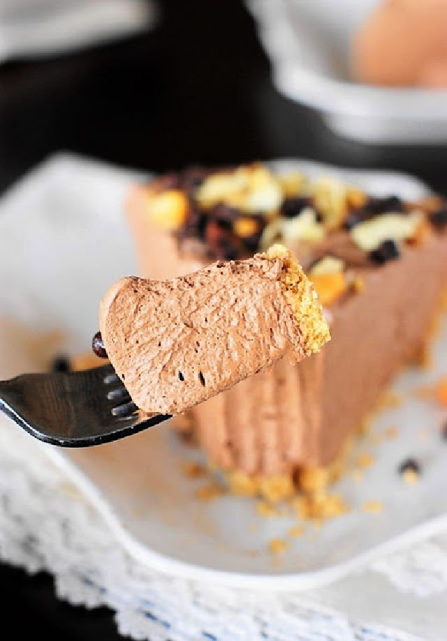 A bite of chocolate mousse pie on a fork in front of the piece of pie.