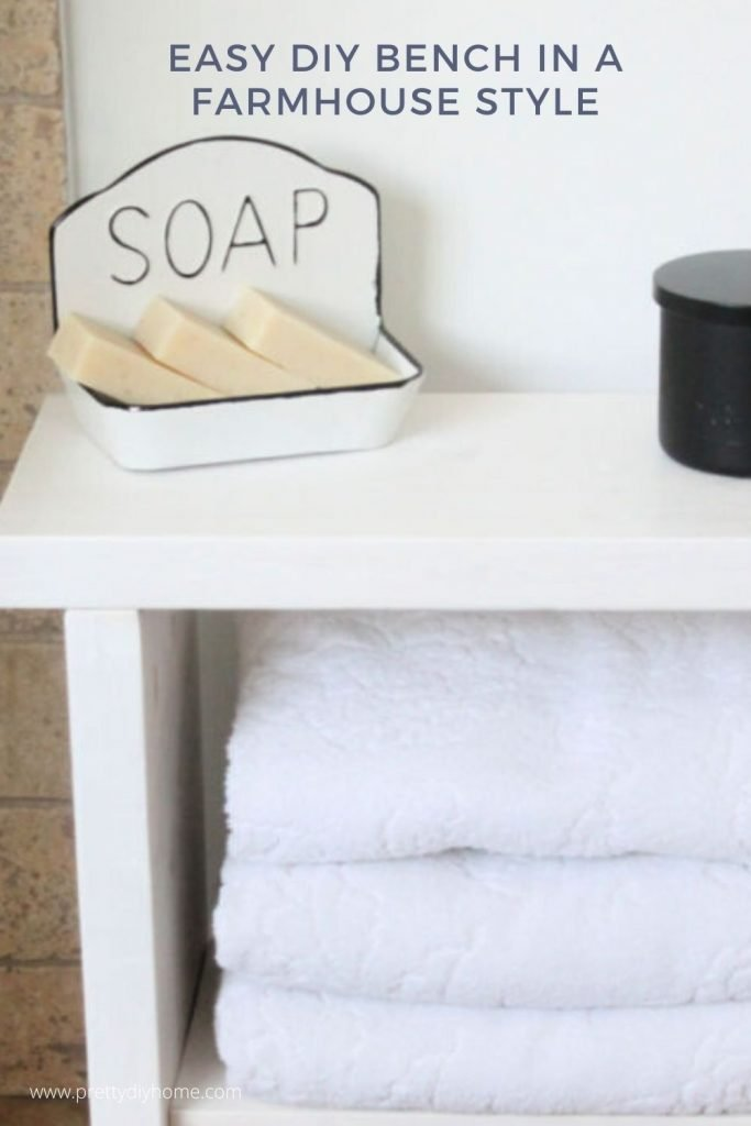 A sturdy DIY Bench made from wood and stained white with a soap dish and black candle in a bathroom.