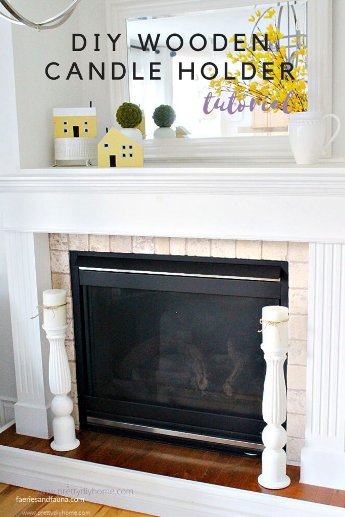 A white fireplace decorated with two large wooden DIY candle holders.