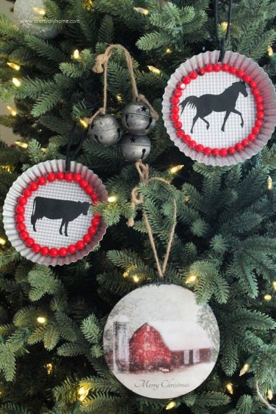 Handmade DIY Christmas ornaments hanging on a tree. They have black farmhouse animals and red berries on a tart tin background.