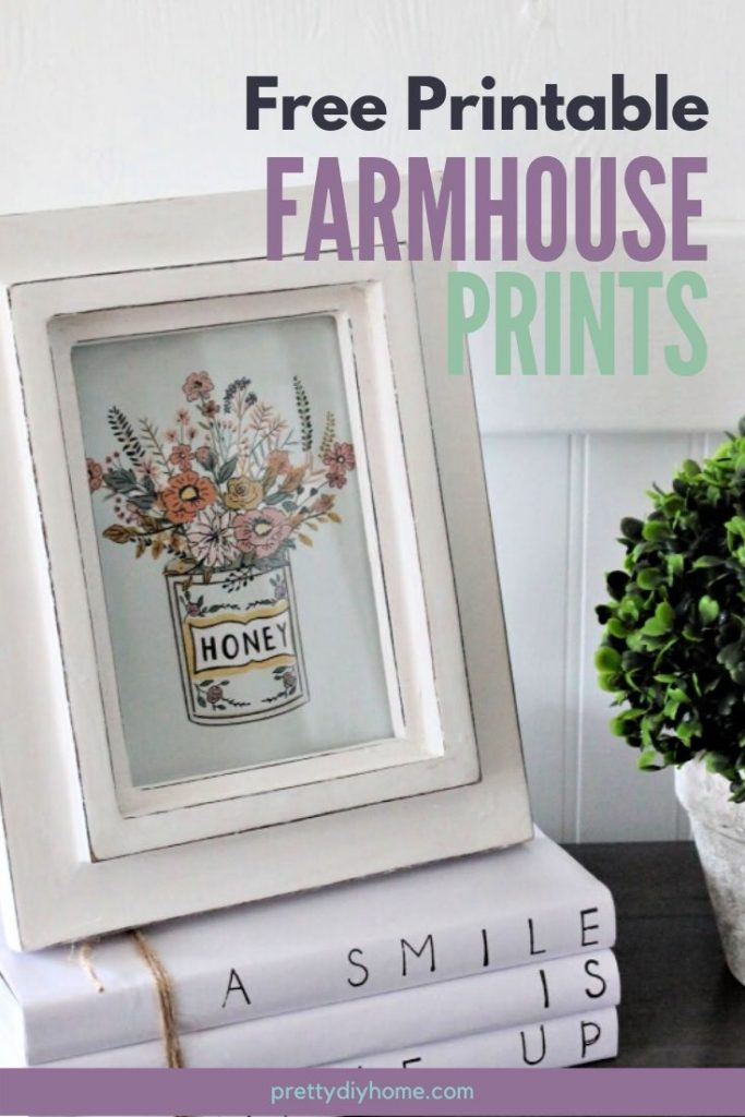 A free farmhouse floral printable in a white frame, sitting on a stack of farmhouse covered book stacks