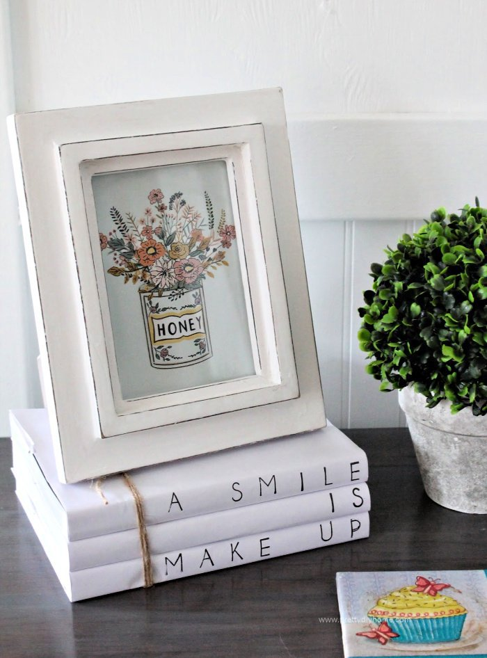 A farmhouse vignette with a free farmhouse printable in a frame, some moss and a farmhouse book stack.