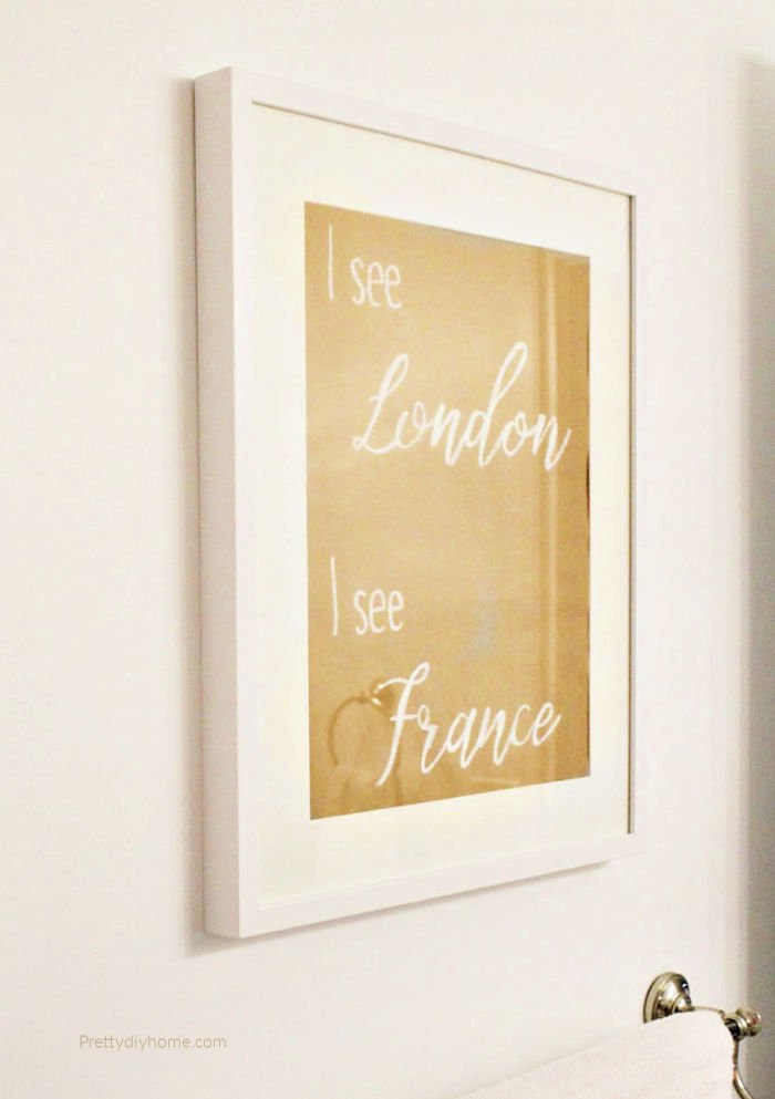 A DIY bathroom sign on brown paper in an IKEA frame that says I See London I See France