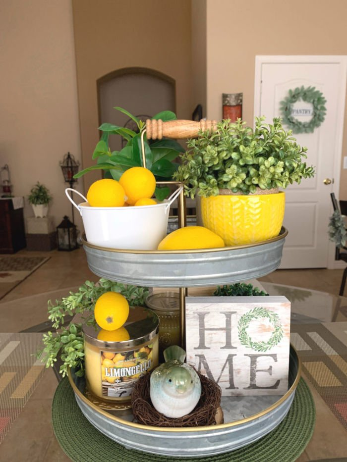 A tiered tray decorated with lemons and bright yellow ornaments for Summer decor.