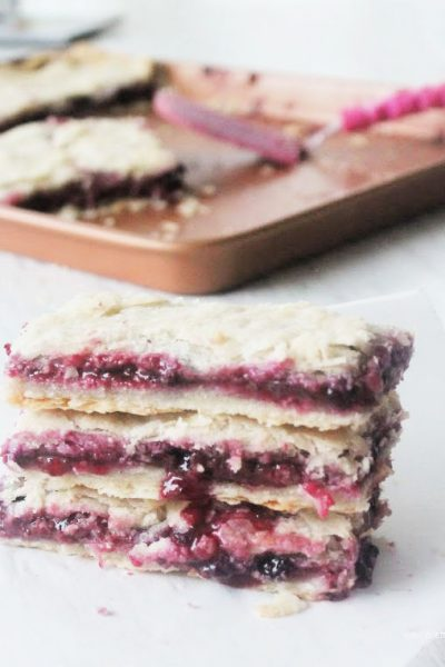 Three stacked pieces of bumbleberry pie made from scratch recipe.