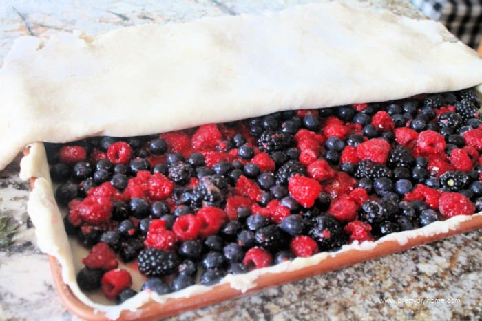 Placing the top layer of pie crust on a bumbleberry slab pie recipe.