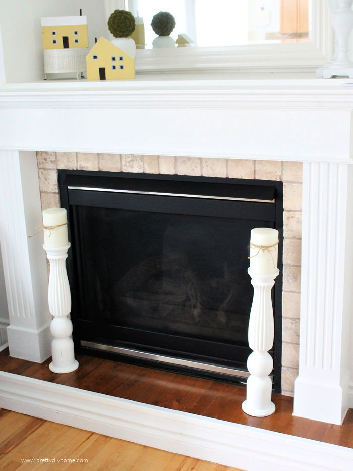 Two tall floor sized DIY candle holders flanking the front of a fireplace.