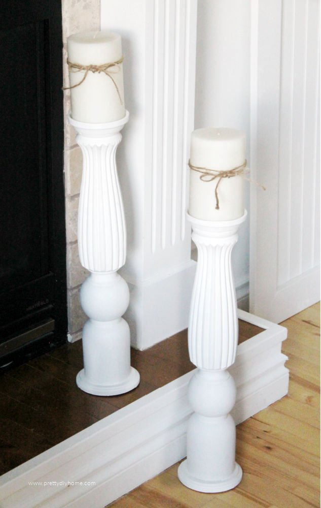Two large floor sized candle holders in white sitting on a fireplace.