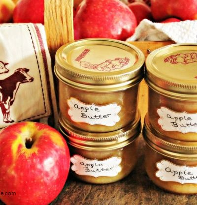 Homemade apple butter canned and labelled into canning jars.