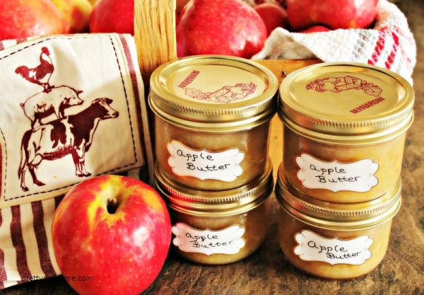 Homemade apple butter in jars with baskets of fresh apples.