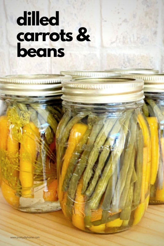 Jars of homemade dilled pickled carrots and beans, pretty in orange and green sitting on a kitchen counter.