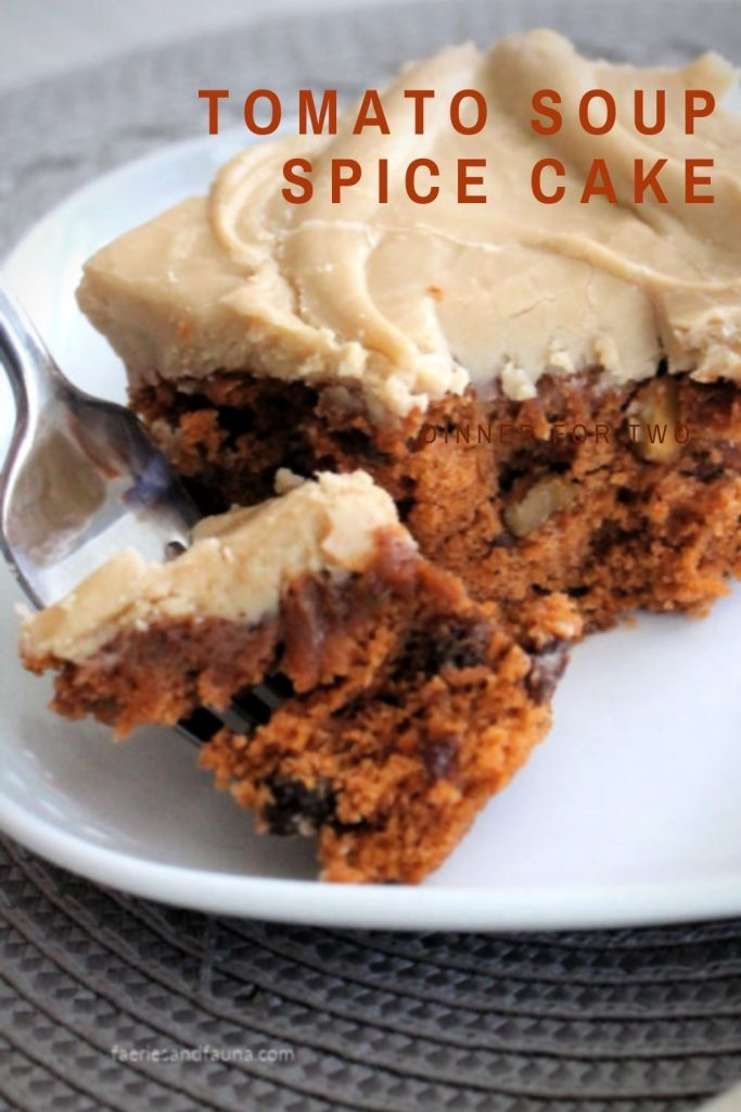 Moist tomato soup cake with raisins and brown sugar icing. The cake is open showing the soft and chewy center.
