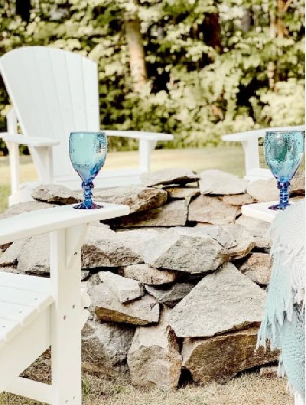 Simple and classic DIY firepit made with rocks and surrounded by white lawn chairs