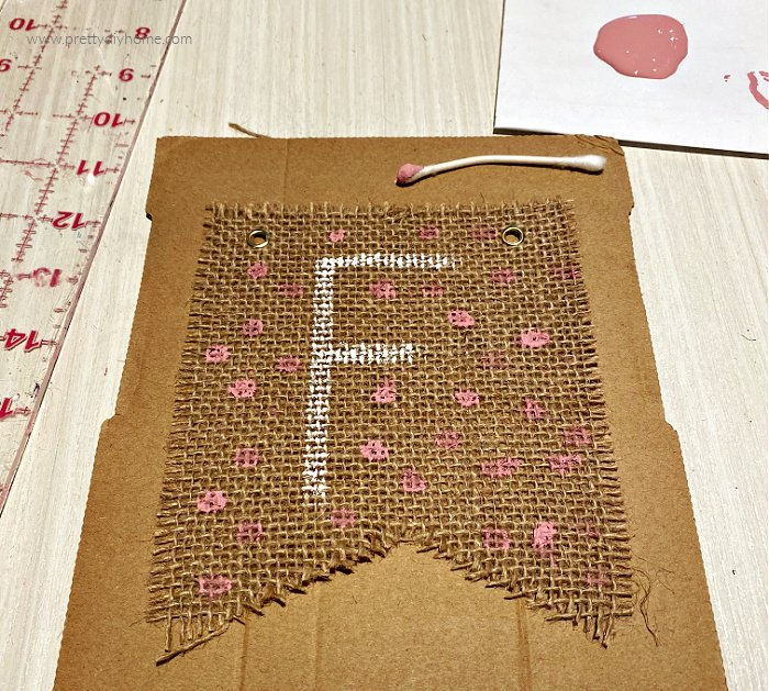 A pink polka dot painted DIY dollar tree burlap banner for Fall with the letter F.