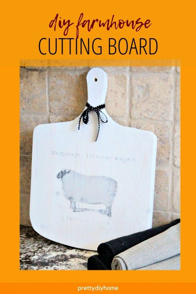 A homemade cutting board in white with a black sheep graphic.