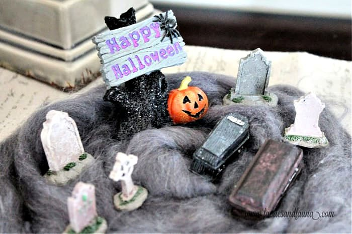 A Halloween Diorama of a grave yard with a miniature coffin, gravestones and Happy Halloween sign.