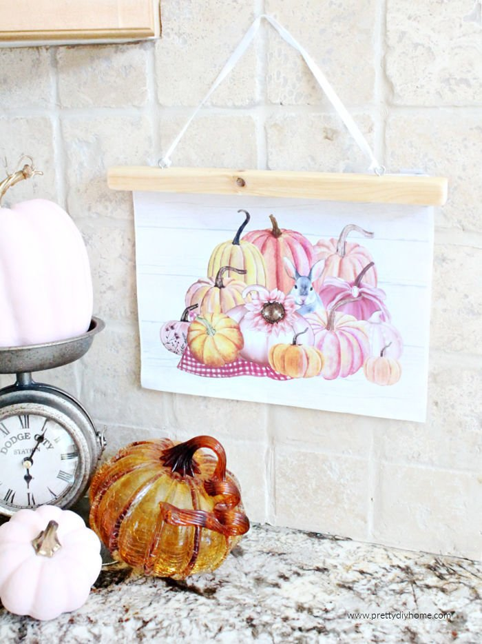 Pink pumpkin farmhouse printable for the kitchen with a stack of pink watercolor pumpkins. The pumpkin fall printable is hanging on the kitchen backsplash with a farmhouse scale.